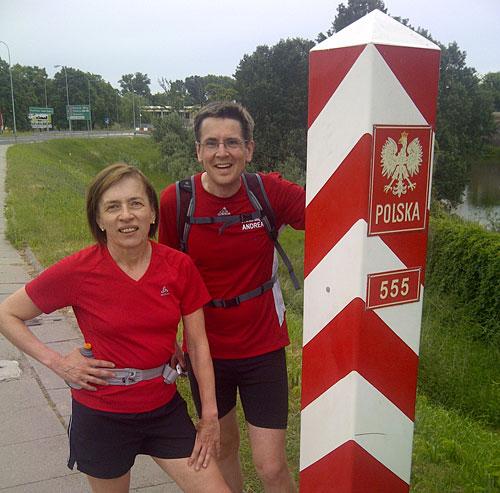 Läuferin und Läufer an rot-weißem polnischen Grenzpfosten