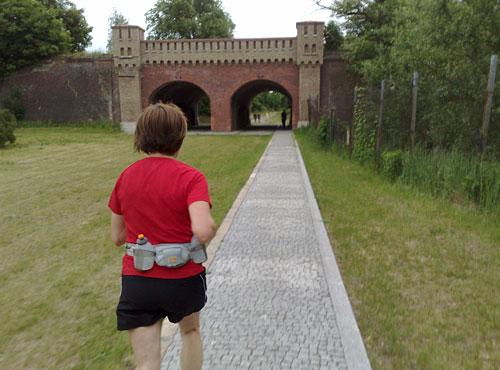 Läuferin läuft auf Berliner Tor in Kostrzyn zu