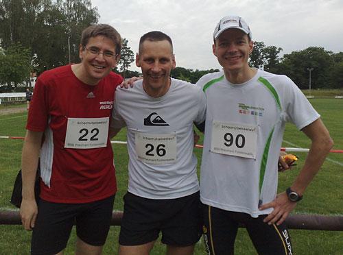 Drei Läufer auf Sportplatz
