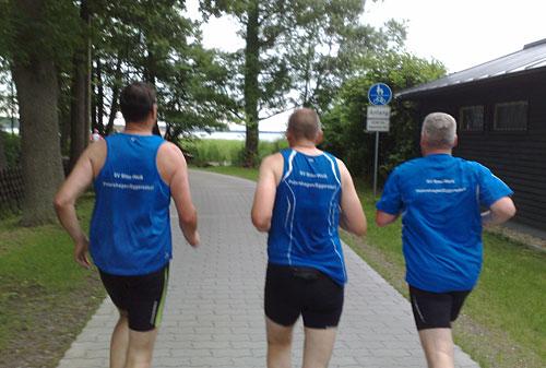 Drei Läufer in blauen Shirts