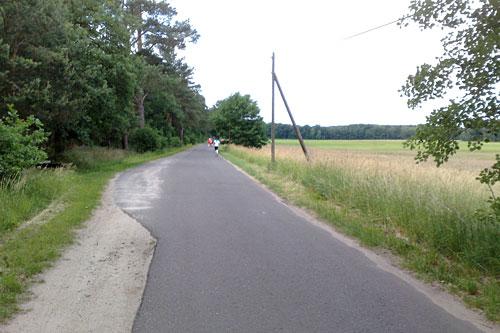 Straße mit Läufern neben Feld