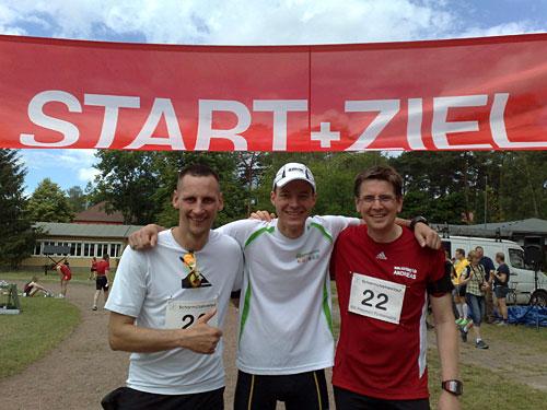 Drei Läufer unter dem Start- und Ziel-Banner des Scharmützelseelaufs