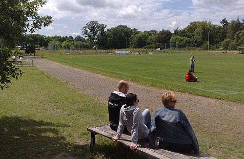 Sportplatz mit Zuschauern und Läuferinnen und Läufern