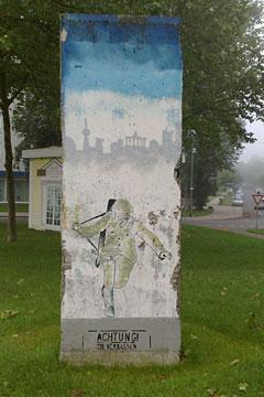 Segment der Berliner Mauer mit über Stacheldraht springenden Soldaten