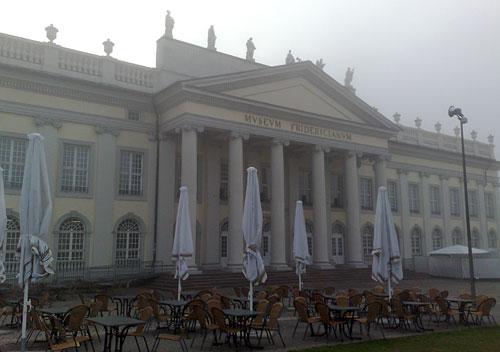 Museum Friedricianum und Café-Stühle und eingeklappte Sonnenschirme davor