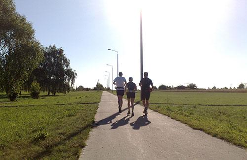 Drei Läufer auf Asphalt-Weg