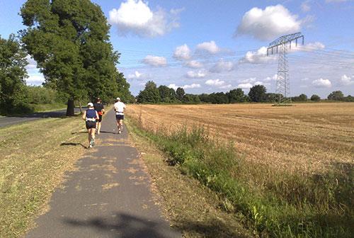 Läufer neben abgeernteten Feld
