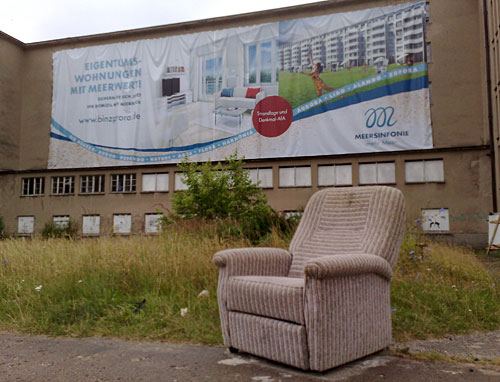 Sessel vor Ruine von Prora mit moderner Werbung für Eigentumswohnungen