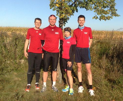 4 Läufer in roten Shirts vor einem Maisfeld