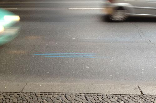 Markierung mit drei blauen Streifen auf einer befahrenen Straße