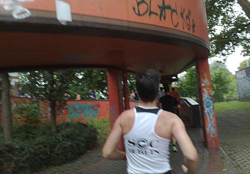 Läufer vor einem schneckenförmig gewundenen Brückenaufgang