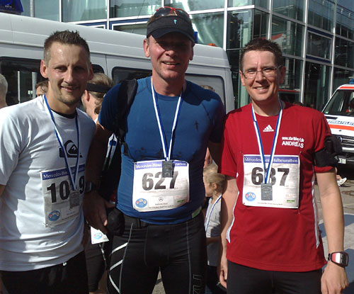 Drei lächelnde Läufer mit Finisher-Medaillen