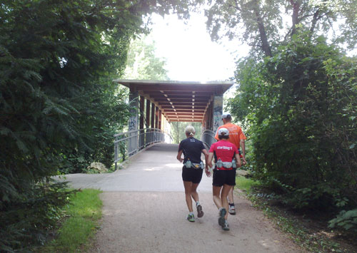 Läuferinnen und Läufer vor Brücke