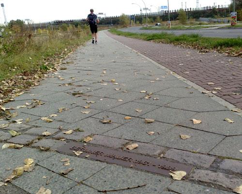 Plakette Berliner Mauer im Gehweg mit Läufer im Hintergrund