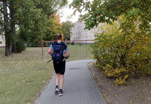 Läufer auf Weg zwischen Häusern