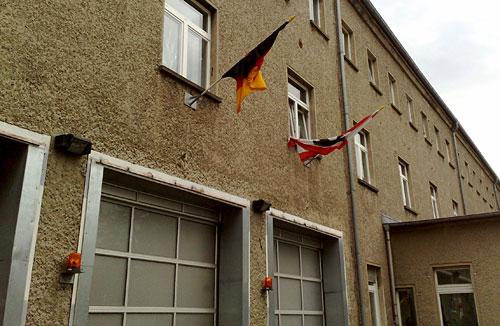 Gebäude mit verwickelter Deutschland- und Berlinfahne