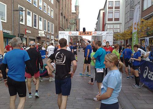 Nur wenige Läuferinnen und Läufer vor dem Startbanner