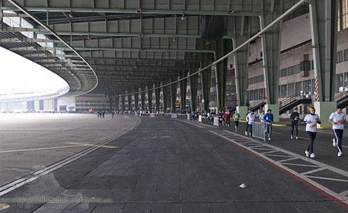 Überdachter Außenbereich eines Hangars mit Marathonstaffel-Läufern