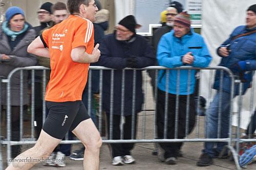 Läufer läuft vorbei an Zuschauern