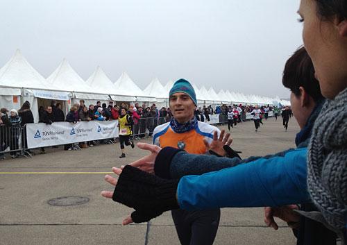 Hände recken sich einem Läufer entgegen