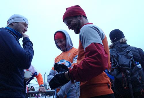 Drei Läufer unterhalten sich lächelnd