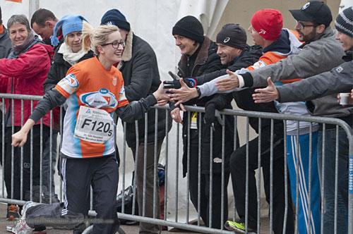 Läuferin klatscht jubelnde Zuschauer im Vorbeilaufen ab