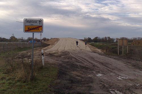 Ortsschild, im Hintergrund Baustelle und Läufer
