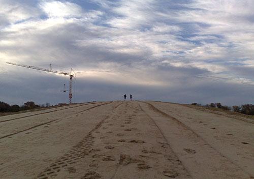 Läufer oben auf Sandberg vor Wolkenhimmel