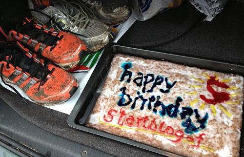 Auto-Kofferraum mit dreckigen Laufschuhen und Kuchen