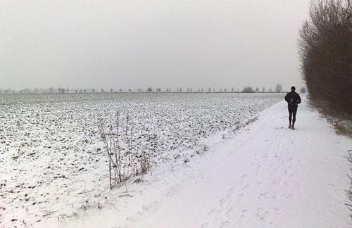 Läufer und weites, verschneites Feld