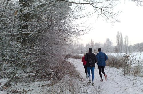 Läuferin und Läufer beim Lauf durch den Schnee