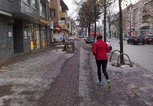 Läuferin in leerer Einkaufsstraße