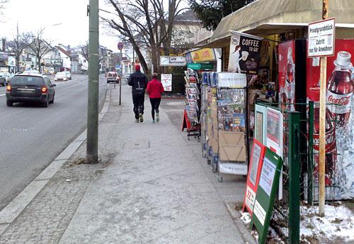 Läuferin und Läufer laufen vorbei an einem Kiosk