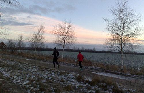 Läuferin und Läufer vor Sonnenaufgang
