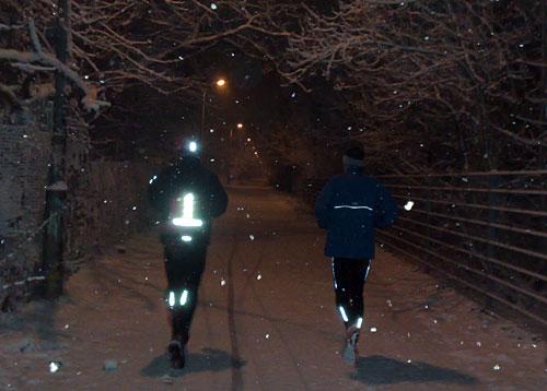 Läufer im Dunkeln bei Schnee