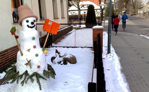 Ein Schneemann grüßt die Läufer vom Wegesrand