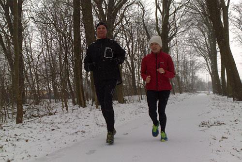 Läuferin und Läufer auf verschneitem Weg