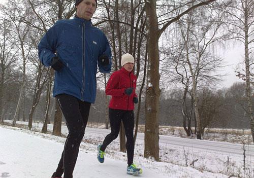 Läuferin und Läufer bei Schneelauf