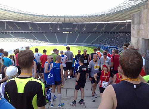 Blick von oben in das Olympiastadion mit Läufern auf der blauen Tartanbahn