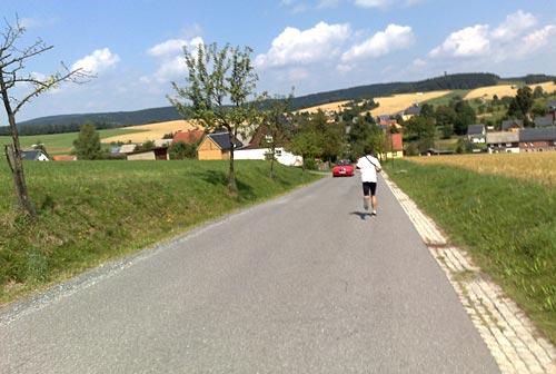 Läufer auf stark abschüssiger Straße nach Hinterhermsdorf