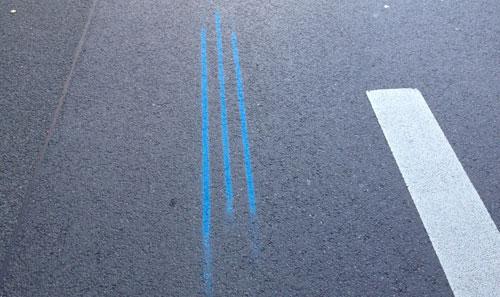 Die drei blauen Marathonstreifen auf dem Asphalt