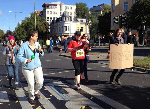 Eine der letzten Läuferinnen wird enorm von ihren Freundinnen unterstützt