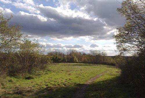 Schmaler Pfad zum Laufen vor imposantem Wolkenhimmel
