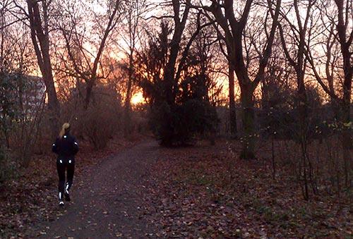 Läuferin im Park bei Sonnenaufgang
