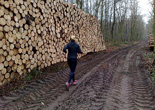 Läuferin neben Holzstoß