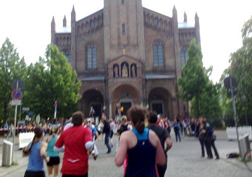 Eine Cheerleader-Gruppe feuert die Läuferinnen und Läufer vor der Kirche St. Peter und Paul an