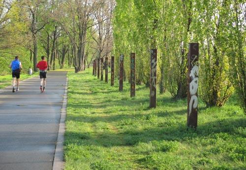Läufer neben Stelen im Park