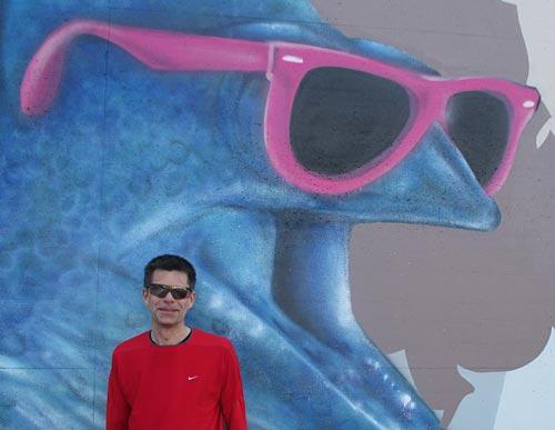 Läufer mit Sonnenbrille vor Grafitti eines Fisches mit Sonnenbrille