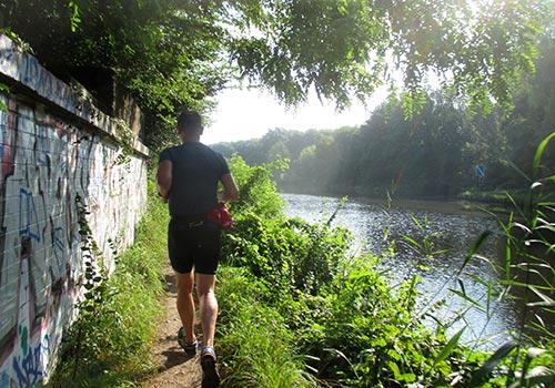 Läufer auf schmalem Pfad entlang des Kanals