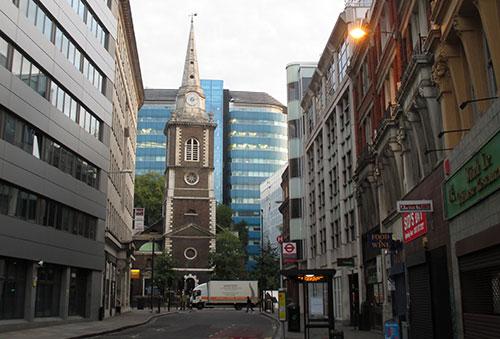Alte Kirche vor Glasfassade eines Hochhauses